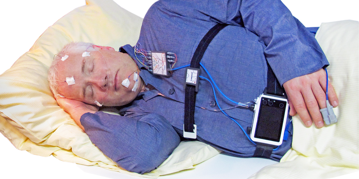 A patient is sleeping wearing a PSG, Polysomnography sleep diagnostic device called SOMNO HD from Somnomedics. The picture shows a built in effort belt and a very small EEG head box. The PSG device is very small and the cables run behind the belt-